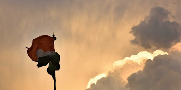 NEW DELHI, INDIA - MARCH 12: The Indian flag makes various forms due to fast winds as dark clouds engulfed the capital on March 12, 2016 in New Delhi, India. Despite the drizzle and heavy rainfall in Delhi, both minimum and maximum temperature rose marginally in Gurgaon. The IMD said the maximum temperature rose to 33 degrees Celsius and it was 2 degrees more than Thursday. The minimum temperature was recorded at 16.9 degrees Celsius, and it was 3 degrees more than the previous day. An official of the IMD said that temperature will fall by 3 to 4 degrees in north-western India as moderate to scattered rainfall is expected in certain parts. (Photo by Saumya Khandelwal/Hindustan Times via Getty Images)