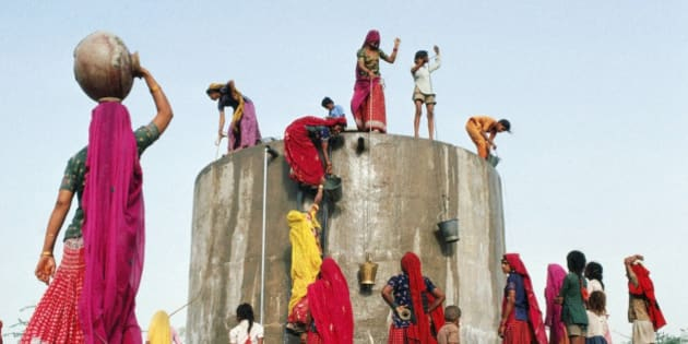 India, Rajasthan,women and children gathering water from concrete well