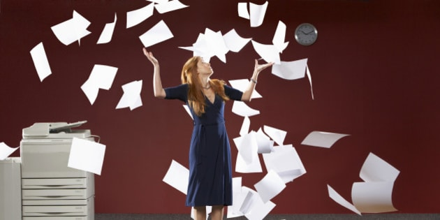 Woman throwing sheets of papers in air