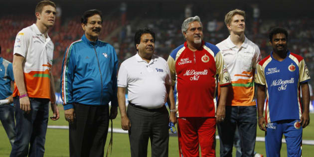 Pune Warriors team owner Subroto Roy, second left, and Royal Challengers Bangalore team owner Vijay Mallya, third right, stand with Indian Premier League (IPL) Chairman Rajiv Shukla, third left, cricketer Muttaiah Muralitharan, right, and Sahara Force India drivers Paul di Resta, left, and Nico Hulkenberg, second right, before the start of the IPL cricket match between Pune Warriors and Royal Challengers Bangalore in Bangalore, India, Tuesday, April 17, 2012. (AP Photo/Aijaz Rahi)