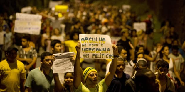 "A protester holds a sign that reads in Portuguese; ""Proud of the people, shame on the politicians,"" as he marches with others from the Rocinha slum towards the house of Rio de Janeiro state governor Sergio Cabral in Rio de Janeiro, Brazil, Tuesday, June 25, 2013. (AP Photo/Victor R. Caivano)"
