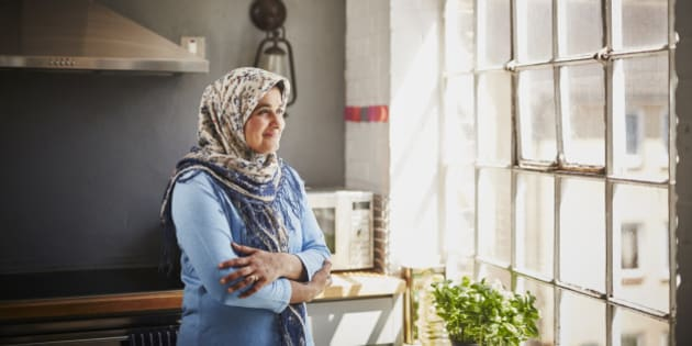 A woman wearing a head scarf smiles whilst looking out of her kitchen window