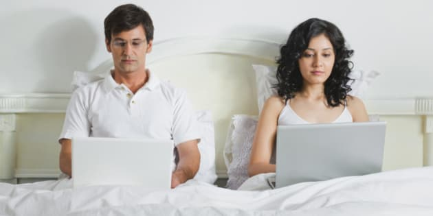 Young couple using laptops in bed