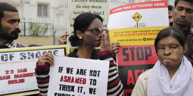 Acid attack victim Laxmi, center, holds placards with others to create awareness during a protest at the spot where she was attacked in 2005, outside the Khan Market Metro station in New Delhi, India, Wednesday, Jan. 22, 2014. (AP Photo/Tsering Topgyal)