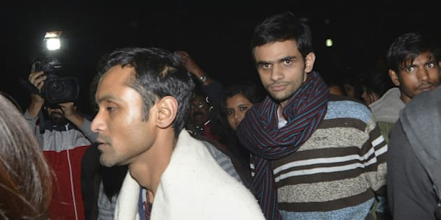 This photograph taken late on February 23, 2016 shows Indian student activist Umar Khalid (C) and Anirban Bhattacharya (L) walking through the campus of New Delhi's Jawaharlal Nehru University (JNU) on their way to surrendering to Indian authorities. Khalid and Bhattacharya are accused of sedition over a rally at which anti-India slogans were shouted.  Students have accused Prime Minister Narendra Modi's right-wing nationalist government of misusing the British-era sedition law to stifle dissent.  AFP PHOTO / AFP / STRDEL        (Photo credit should read STRDEL/AFP/Getty Images)