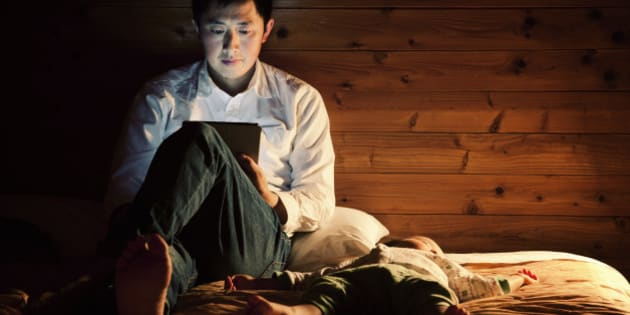 An asian father using a tablet pc on the bed at night, his baby boy sleeping by his side.