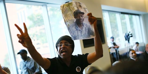TORONTO, ON - SEPTEMBER 1: Cecil Peter holds up a photo of Andrew Loku, who last month was shot by police and later died of his injuries, at a carding consultation meeting at the Toronto Reference Library.        (Cole Burston/Toronto Star via Getty Images)