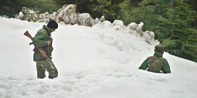 Indian Army soldiers patrol near the Jammu-Srinagar highway in Patnitop, about 110 kilometers (69 miles) northeast of Jammu, India, Wednesday, march 2, 2005. The highway connecting Kashmir to the rest of India reopened Tuesday after being blocked for three weeks by heavy snowfall, landslides and avalanches that left at least 310 people dead on the Indian side of the Himalayan territory, police said. (AP Photo/Channi Anand)