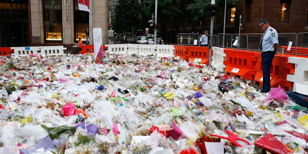 SYDNEY, AUSTRALIA - DECEMBER 23: (AUSTRALIA & NEW ZEALAND OUT) A Police officer watches flowers before being removed from the Memorial of the victims of the siege in Martin Place on December 23, 2014 in Sydney, Australia. Volunteers have gathered at Martin Place this morning to begin clearing the thousands of bouquets and cards left in tribute to Tori Johnnson and Katrina Dawson, who were killed in last week's hostage siege at the Lindt Cafe. (Photo by Daniel Munoz/Fairfax Media via Getty Images)