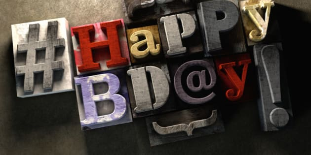 Happy Birthday title in vintage colorful wood block text. Social media hastag with grunge concrete background. Rough wooden blocks celebration of bday.
