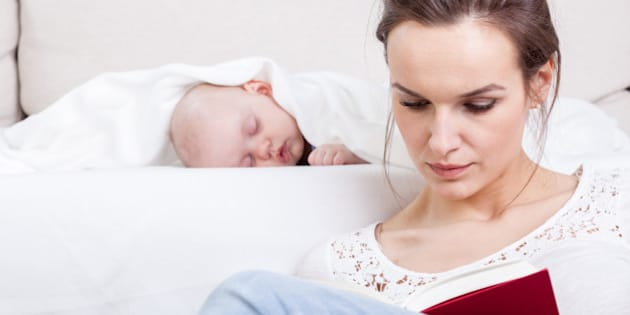 Mother reading a book while baby's sleeping