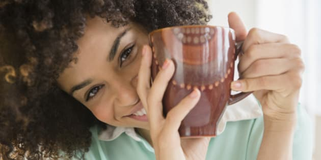 Mixed race woman drinking cup of coffee