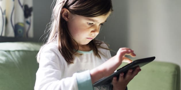 A young girl uses a tablet computer late at night with the glow from the screen on her face.