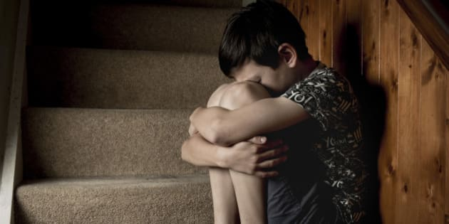 Sad, bullied or abused boy crying sitting on stairs
