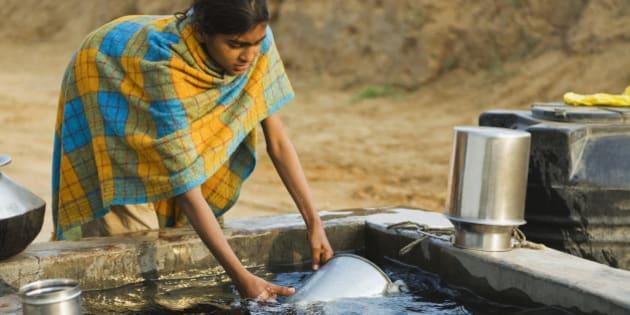 Girl cleaning pots in a tube well reservoir, Farrukh Nagar, Gurgaon, Haryana, India