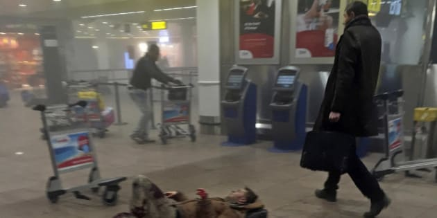 In this photo provided by Georgian Public Broadcaster and photographed by Ketevan Kardava, an injured man lies on the floor in Brussels Airport in Brussels, Belgium, after explosions were heard Tuesday, March 22, 2016. A developing situation left a number dead in explosions that ripped through the departure hall at Brussels airport Tuesday, police said. All flights were canceled, arriving planes were being diverted and Belgium's terror alert level was raised to maximum, officials said. (Ketevan Kardava/ Georgian Public Broadcaster via AP)