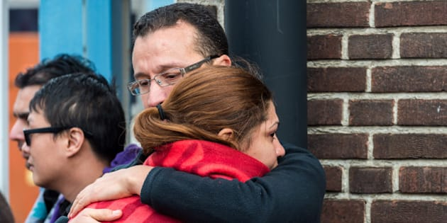 People comfort each other after being evacuated from Brussels airport, after explosions rocked the facility in Brussels, Belgium, Tuesday March 22, 2016. Authorities locked down the Belgian capital on Tuesday after explosions rocked the Brussels airport and subway system, killing at least 13 people and injuring many more. Belgium raised its terror alert to its highest level, diverting arriving planes and trains and ordering people to stay where they were. Airports across Europe tightened security. (AP Photo/Geert Vanden Wijngaert)