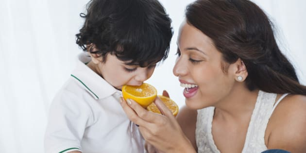 Woman feeding orange to her son