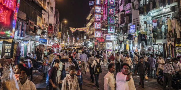 Delhi, India - October 11, 2015: People walking in Main Bazaar street of Paharganj at night Delhi India. This neighbourhood of Central Delhi is well known as a commercial area and also were hundreds of affordable hostels, restaurants and hotels are located.