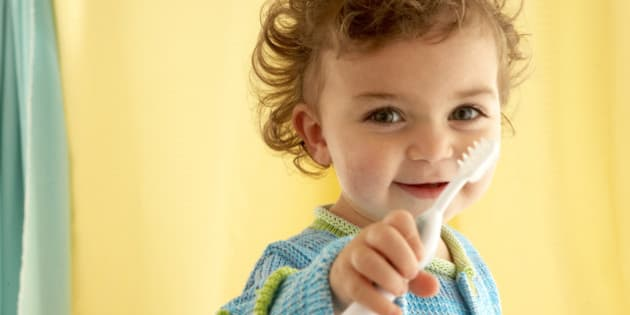 Girl (21-24 months) holding toothbrush, portrait