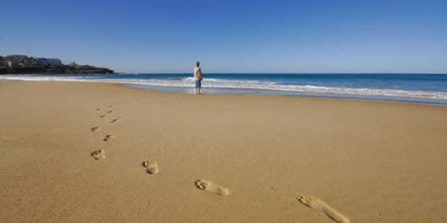Woman standing a lone on a beach.