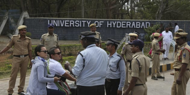 Policemen stand guard as security men check the identity cards of students arriving at the Hyderabad University in Hyderabad, in India, Tuesday, Jan 19, 2016. Hundreds of students on Tuesday angrily protested the death of an Indian student who, along with four others, was barred from using some facilities at his university in the southern tech-hub of Hyderabad. The protesters accused Hyderabad University's vice chancellor along with a federal minister of unfairly demanding punishment for the five lower-caste students after they clashed last year with a group of students supporting the governing Hindu nationalist party. (AP Photo /Mahesh Kumar A.)