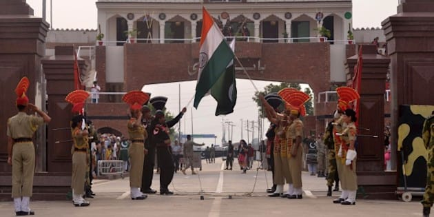 Pakistani Rangers and Indian Border Security Force personnel lower their respective country flags at the Beating Retreat Ceremony at the India-Pakistan Wagah Border Post on March 24, 2016. / AFP / NARINDER NANU        (Photo credit should read NARINDER NANU/AFP/Getty Images)