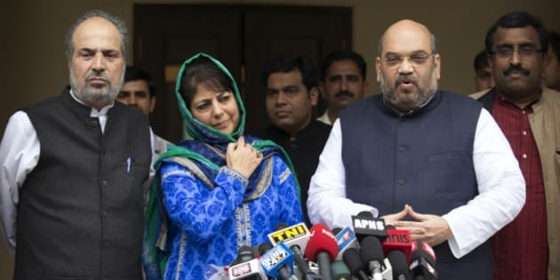 India's ruling Bharatiya Janata Party (BJP) president Amit Shah, right, addresses the media after a meeting with Kashmir's regional Peoples' Democratic Party (PDP) leader Mehbooba Mufti, second left in blue, in New Delhi, India, Tuesday, Feb. 24, 2015. The BJP and the PDP Tuesday finalized an agreement to form a coalition government in Kashmir, the first time the Hindu nationalist party will share a leadership position in the predominantly Muslim region. (AP Photo / Manish Swarup)