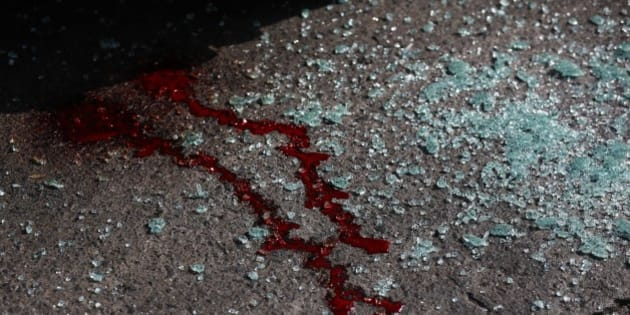 FILE - In this March 3, 2014 file photo, blood and shattered glass cover the pavement after gunmen opened fire on the driver of a passenger bus, Roger Enrique Hernandez Gutierrez, and his assistant, killing them both in Tegucigalpa, Honduras. Taxi and passenger bus drivers are targets of gangs seeking extortion money in this country with one of the highest murder rates in the world. (AP Photo/Dario Lopez-Mills, File)
