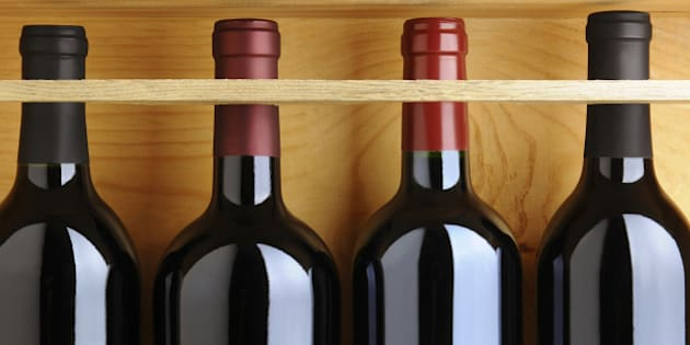 Closeup of four red wine bottles in a wooden case.