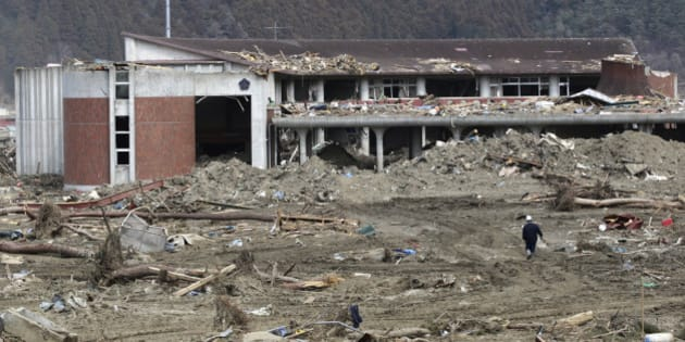 A police officer walks towards the tsunami-hit Okawa Elementary School in Ishinomaki, Miyagi Prefecture, northeastern Japan March 29, 2011. Only 34 students out of a total of 108 survived the disaster.   REUTERS/Yuriko Nakao (JAPAN - Tags: DISASTER ENVIRONMENT)