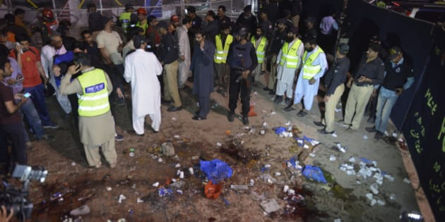 Pakistani rescuers and officials gather at a bomb blast site in Lahore on March 27, 2016.