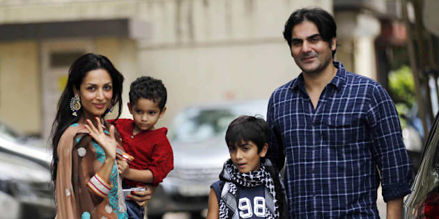 Indian Bollywood film actor Malaika Arora Khan (L), with husband Arbaz khan and sons, greets well-wishers outside her residence during Eid al-Fitr in Mumbai on August 20, 2012.     AFP PHOTO        (Photo credit should read STR/AFP/GettyImages)