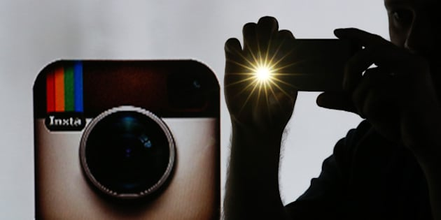 A man takes a photograph with a mobile device whilst standing against an illuminated wall bearing Instagram Inc.'s logo in this arranged photograph in London, U.K., on Tuesday, Jan. 5, 2016. Instagram Inc. provides mobile phone-based photography sharing services. Photographer: Chris Ratcliffe/Bloomberg via Getty Images