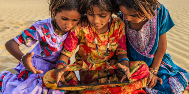 Happy Indian little girls sitting on a sand dune and using tablet in desert village, Thar Desert, Rajasthan, India.