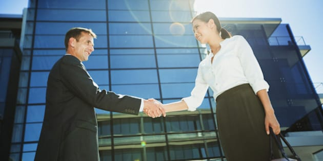 Businessman and businesswoman shaking hands below highrise