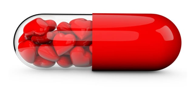 3D render of a pill tablet filled with red love hearts