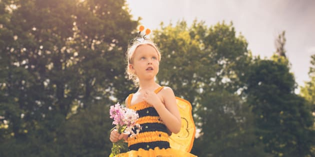 A child dressed as a Bumblebee looks up in a stoic pose with a handful of wildflowers.