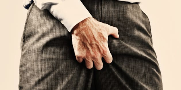 Cropped view of businessman in formal clothes grabbing his genitals through his clothes, maybe he's itchy but it's very vulgar behavior and sexist too!
