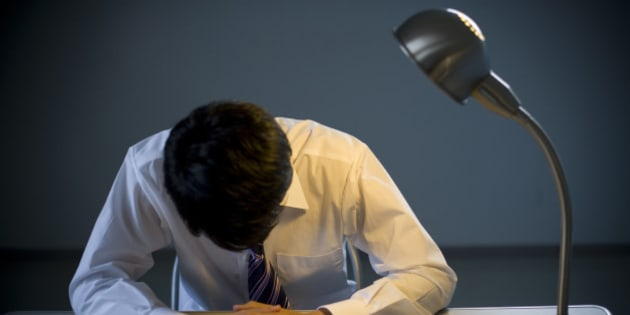 Young Businessman Hanging His Head In Interrogation Room