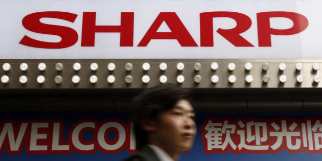 A logo of Sharp Corp is seen above a Chinese tourist standing outside an electronics retail store in Tokyo, Japan, March 30, 2016. REUTERS/Yuya Shino