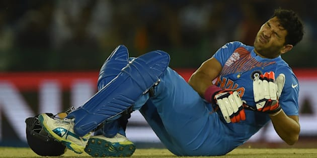 India's Yuvraj Singh grimaces in pain during the World T20 cricket tournament match between India and Australia at The Punjab Cricket Stadium Association Stadium in Mohali on March 27, 2016. / AFP / MONEY SHARMA        (Photo credit should read MONEY SHARMA/AFP/Getty Images)