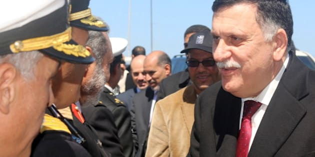 Libyan Prime Minister-designate Fayez Seraj (R) is greeted upon arrival in Tripoli, Libya March 30, 2016. REUTERS/Hani Amara