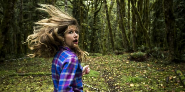 A woman running scared through a dense forest.