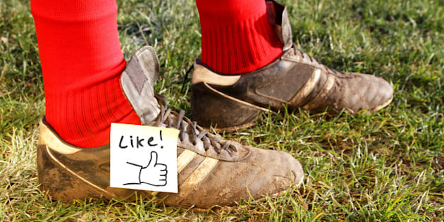 'Like' symbol on football players boots, while standing in a field ready to play.