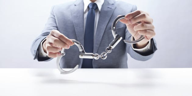 Businessman holding handcuffs at the desk.