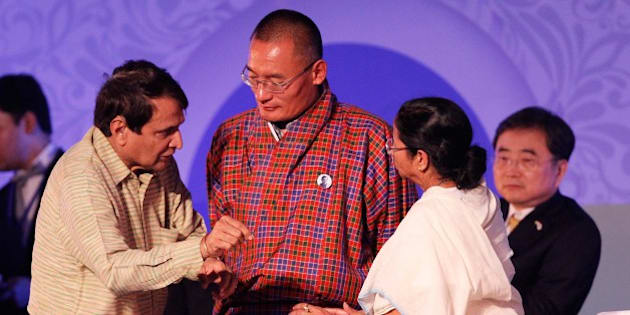 """KOLKATA, INDIA - JANUARY 8: Prime Minister of Bhutan Tshering Tobgay, West Bengal Chief Minister Mamata Banerjee and Railways Minister Suresh Prabhu during the inaugural function of Bengal Global Business Summit, at Milan Mela Ground on January 8, 2015 in Kolkata, India. The Bengal Global Business Summit is designed to attract the investor community to the cash-strapped state. During the function, Finance Minister Arun Jaitley said, """"If Bengal followed such a strong economic growth policy, it would be able to generate jobs and revenue needed to fight poverty, else would have to fall back on shallow political slogans."""" (Photo by Ashok Nath Dey/Hindustan Times via Getty Images)"""