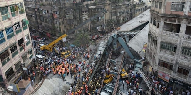 Indian rescue workers and volunteers try to free people trapped under the wreckage of a collapsed fly-over bridge in Kolkata on March 31, 2016.