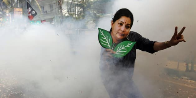 A supporter of the All India Anna Dravida Munnetra Kazhagam (AIADMK) holds a cutout of the party leader Jayaram Jayalalitha as he celebrates with firecrackers the early lead of their party in Tamil Nadu state, in Chennai, India, Friday, May 16, 2014. Jayalalitha's AIADMK was leading in most of the 39 seats in her state.  (AP Photo/Arun Sankar K.)