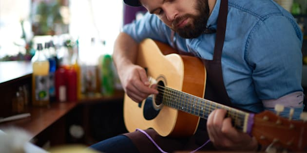 Bearded bartender playing guitar